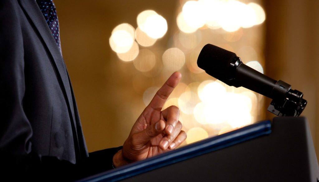 0519-0908-0820-3533_close_up_of_a_man_making_a_point_during_a_speech_microphone_and_podium_in_view_o