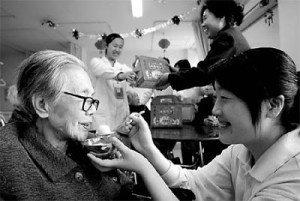 An elderly woman enjoys sweet dumplings at a nursing home in Beijing.