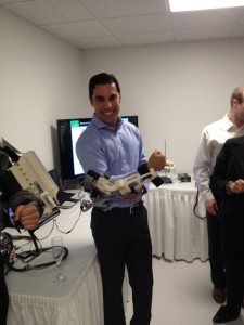 Dr. Azim Jamal, President/CEO of Retirement Concepts demonstrating how an exoskeleton for bimanual therapy functions