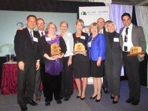 Award Recipients, Hon. Terry Lake, MLAs, & CEO Daniel Fontaine gather on stage for a group photo at 2015 BC Care Awards